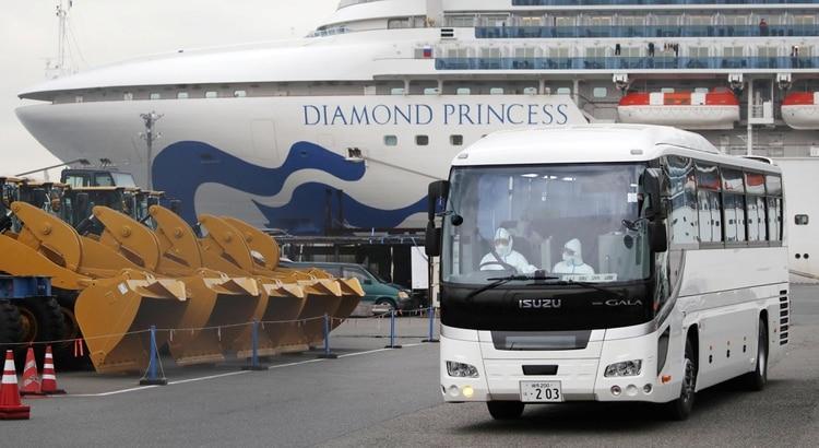 Un conductor con trajes protectores dentro de un autobús que se cree que transporta a pasajeros ancianos del crucero Diamond Princess, donde docenas de pasajeros dieron positivo por coronavirus, en la Terminal de Cruceros del Muelle Daikoku en Yokohama, al sur de Tokio (Kyodo/vía REUTERS)