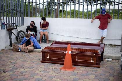 Personas esperan al lado de cajones fúnebres en el Hospital General Guasmo Sur luego de que Ecuador reportara nuevos casos de la enfermedad de coronavirus (COVID-19), en Guayaquil, Ecuador 1 de abril del 2020 (REUTERS/Vicente Gaibor del Pino)