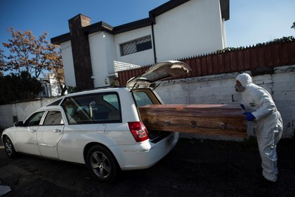 A funeral worker carries a coffin to a hearse before going to pick up a deceased COVID-19 to be buried in Santiago, Chile.  EFE