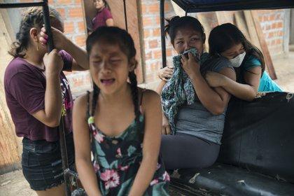 En esta foto del 31 de agosto de 2020 familiares lamentan el fallecimiento de Manuela Chávez a la edad de 88 años, mientras un equipo del gobierno se prepara para sacar su cuerpo del interior de su casa, en el Shipibo, en la región Ucayali de Perú. (Foto AP / Rodrigo Abd, archivo)