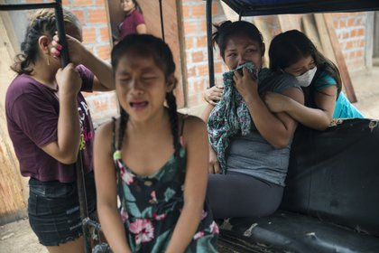 En esta foto del 31 de agosto de 2020 familiares lamentan el fallecimiento de Manuela Chávez, quien falleció por coronavirus a la edad de 88 años, mientras un equipo de gobierno se prepara para sacar su cuerpo del interior de su casa, en el Shipibo en la región Ucayali de Perú. (Foto AP / Rodrigo Abd, archivo)
