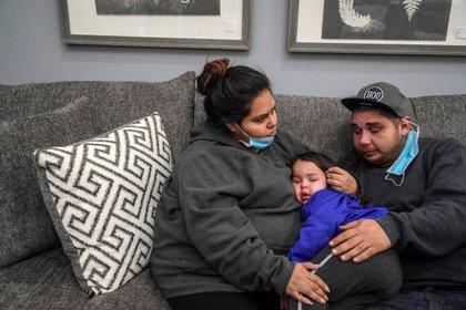 Patrick Youngblood (derecha) y su esposa Marisol abrazan a su hija Audrey en el local de Gallery Furniture, que se transformó en un refugio (REUTERS/Go Nakamura)
