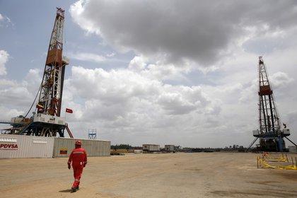 Imagen de archivo de un trabajar petrolero camninando junto a plataformas perforadoras en un campo de crudo operado por la estatal venezolana PDVSA, en la Faja del Orinoco, en el estado de Monagas, Venezuela, Abril 16, 2015. REUTERS/Carlos Garcia Rawlins/