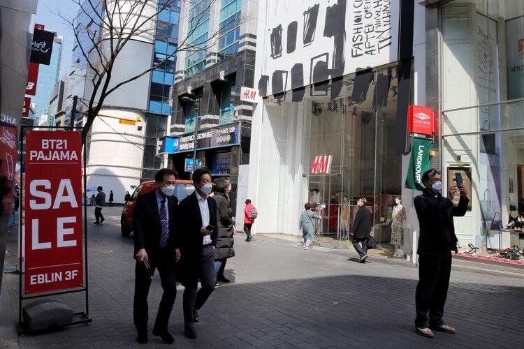 Hombres con máscaras para prevenir el contagio del coronavirus caminan por un distrito comercial en Seúl, Corea del Sur, el 23 de marzo de 2020 (REUTERS/Heo Ran)