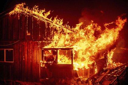 Las llamas se disparan desde una casa mientras el fuego arde a través del área de Berry Creek en el condado de Butte, California, el miércoles 9 de septiembre de 2020 (Foto AP/Noah Berger)