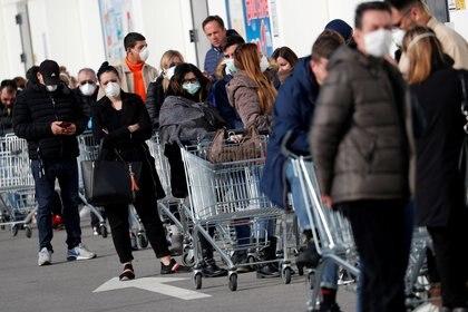 La gente hace cola en un supermercado en las afueras de la ciudad de Casalpusterlengo, que ha sido cerrado por el gobierno italiano debido a un brote de coronavirus en el norte de Italia, el 23 de febrero de 2020 (REUTERS/Guglielmo Mangiapane/File Photo)