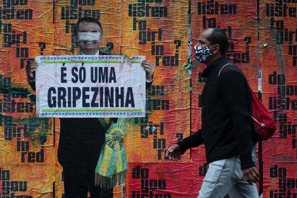 Un ciudadano camina hoy junto a una imagen del presidente brasileño Jair Bolsonaro sosteniendo un cartel con su polémico comentario sobre la COVID-19 al inicio de la pandemia. EFE/Fernando Bizerra