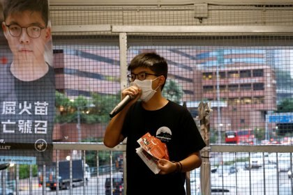 El activista a favor de la democracia Joshua Wong distribuye folletos que animan a la gente a enviar postales a doce residentes de Hong Kong detenidos en China continental después de intentar huir a Taiwán, en Hong Kong. REUTERS/Tyrone Siu