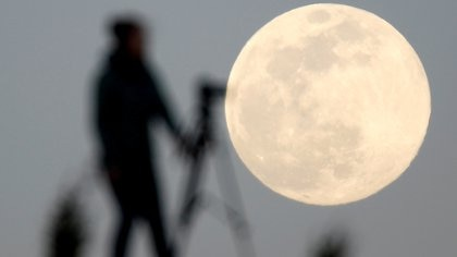 FILE PHOTO: A woman photographs the Pink Supermoon over mountain Smetovi, during an astronomical event that occurs when the moon is closest to the Earth in its orbit, making it appear much larger and brighter than usual, in Zenica, Bosnia and Herzegovina, April 7, 2020. REUTERS/Dado Ruvic/File Photo