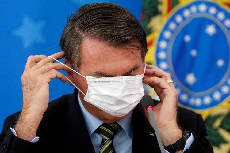 Jair Bolsonaro se ajusta su mascarilla protectora durante una conferencia de prensa en Brasilia, el 18 de marzo de 2020. (REUTERS/Adriano Machado/Foto de archivo)