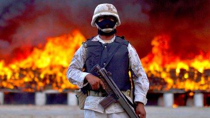 Un soldado custodia la quema de paquetes de marihuana en Tijuana, en cotubre de 2010 (AP)