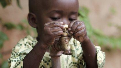 Un niño africano prueba el agua potable al que su población ahora tiene acceso (Shutterstock)