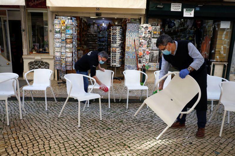 Trabajadores limpiando sillas para abrir la terraza de un restaurante en el primer día de la reapertura tras el cierre del país, en medio de la pandemia de la enfermedad del coronavirus (COVID-19), en Lisboa, Portugal, el 5 de abril de 2021. REUTERS/Pedro Nunes