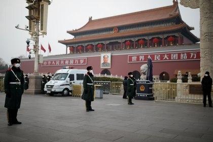 Soldados con máscaras patrullan la plata Tiananmen, en Beijing. Foto: REUTERS/Carlos Garcia Rawlins
