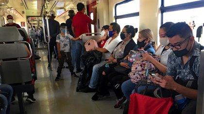 """AME3811. CIUDAD DE MÉXICO (MÉXICO), 22/07/2020.- Fotografía fechada el 21 de julio de 2020 que muestra pasajeros del tren suburbano mientras son vistos con tapabocas en Ciudad de México (México). Superados los 40.000 muertos y 350.000 casos de COVID-19 en México, el control de la pandemia está en duda en el territorio, aunque el Gobierno insiste que la pandemia """"va a la baja"""". EFE/Jorge Núñez."""