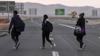 Reinaldo, 26, Anyier, 40, y su hija Danyierly, 14, caminan por la carretera camino a Iquique, luego de cruzar desde Bolivia, en Colchane, Chile, el 18 de febrero de 2021 (MARTIN BERNETTI / AFP)
