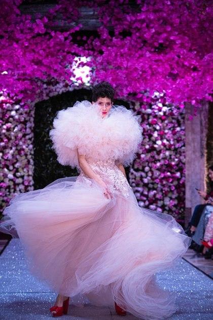 El diseñador se caracteriza por sus diseños realizados en tul, sedas y bordados. En pasarela, un vestido con volumen en el cuello confeccionado en tul rosa