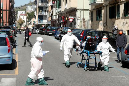 Personal médico con trajes protectores trasladando a un paciente con coronavirus en Nápoles.  Abril 2, 2020. REUTERS/Ciro De Luca