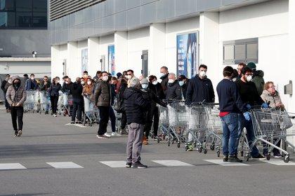 Larguísimas filas de clientes afuera de un supermercado en Casalpusterlengo (REUTERS/Guglielmo Mangiapane)