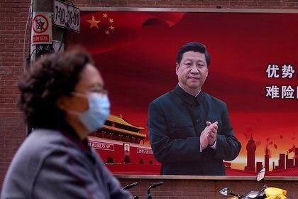 Una mujer con mascarilla camina junto al retrato del presidente chino Xi Jinping (REUTERS/Aly Song)