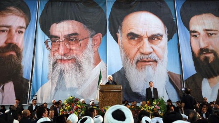 El presidente iraní Hasan Rohani con la imagen de los líderes supremos de fondo (AFP)
