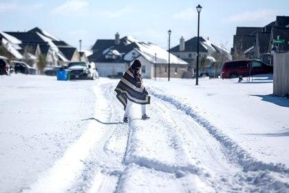Un hombre camina en un vecindario sin electricidad en Pflugerville, Texas, EE. UU. El 15 de febrero de 2021. Fotografía tomada el 15 de febrero de 2021. Bronte Wittpenn / Austin American-Statesman / USA Today Network vía REUTERS