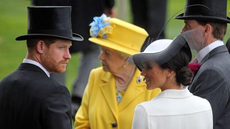 La reina Isabel II, el príncipe Harry y su esposa, la talentosa actriz Meghan Markle, durante una carrera de caballos en junio de 2018 (Shutterstock)