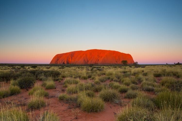 Uluru, también conocido como Ayers Rock, es una impresionante formación rocosa ubicada en una región particularmente remota del Outback australiano. La roca refleja brillantemente los hermosos tonos del amanecer y el atardecer en el vasto paisaje desértico