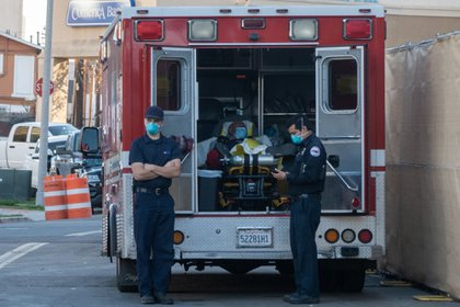EMTs wait with a patient inside an ambulance outside the ER of a hospital in San Diego, California.
