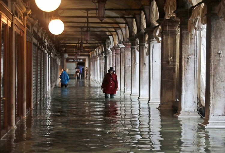 La gente vadea a través del agua causada por una marea alta en Venecia (Foto AP/Luca Bruno)
