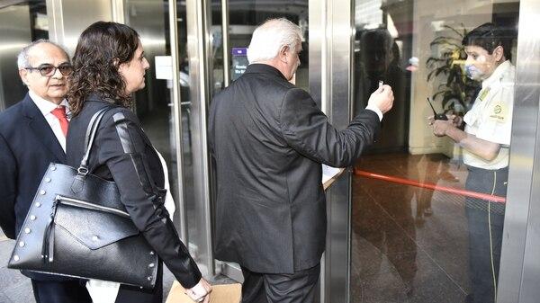 El fiscal Miguel Ángel Osorio (de corbata roja) ingresa al procedimiento en la sede central del Banco Finansur