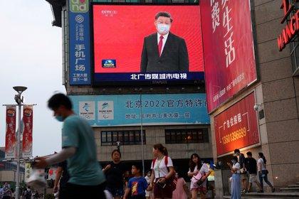 En todas partes. Personas con mascarillas pasan frente a una pantalla gigante que muestra imágenes de noticias del presidente chino Xi Jinping con una mascarilla, en una zona comercial en Beijing (Reuters)