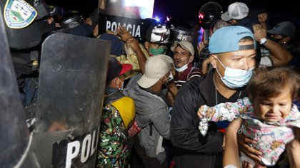 Honduran security forces try to keep migrants who are trying to reach the U.S. from crossing the border in El Florido, Honduras into Guatemala, late Friday, Jan. 15, 2021. (AP Photo/Delmer Martinez)