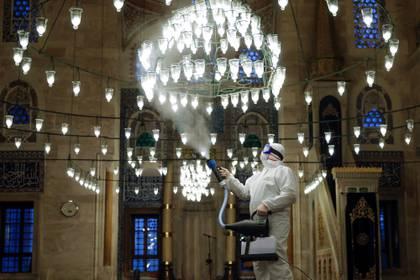 Un trabajador del municipio con un traje protector desinfecta la mezquita Kilic Ali Pasa debido a preocupaciones por el coronavirus en Estambul, Turquía, 11 de marzo de 2020 (Reuters)
