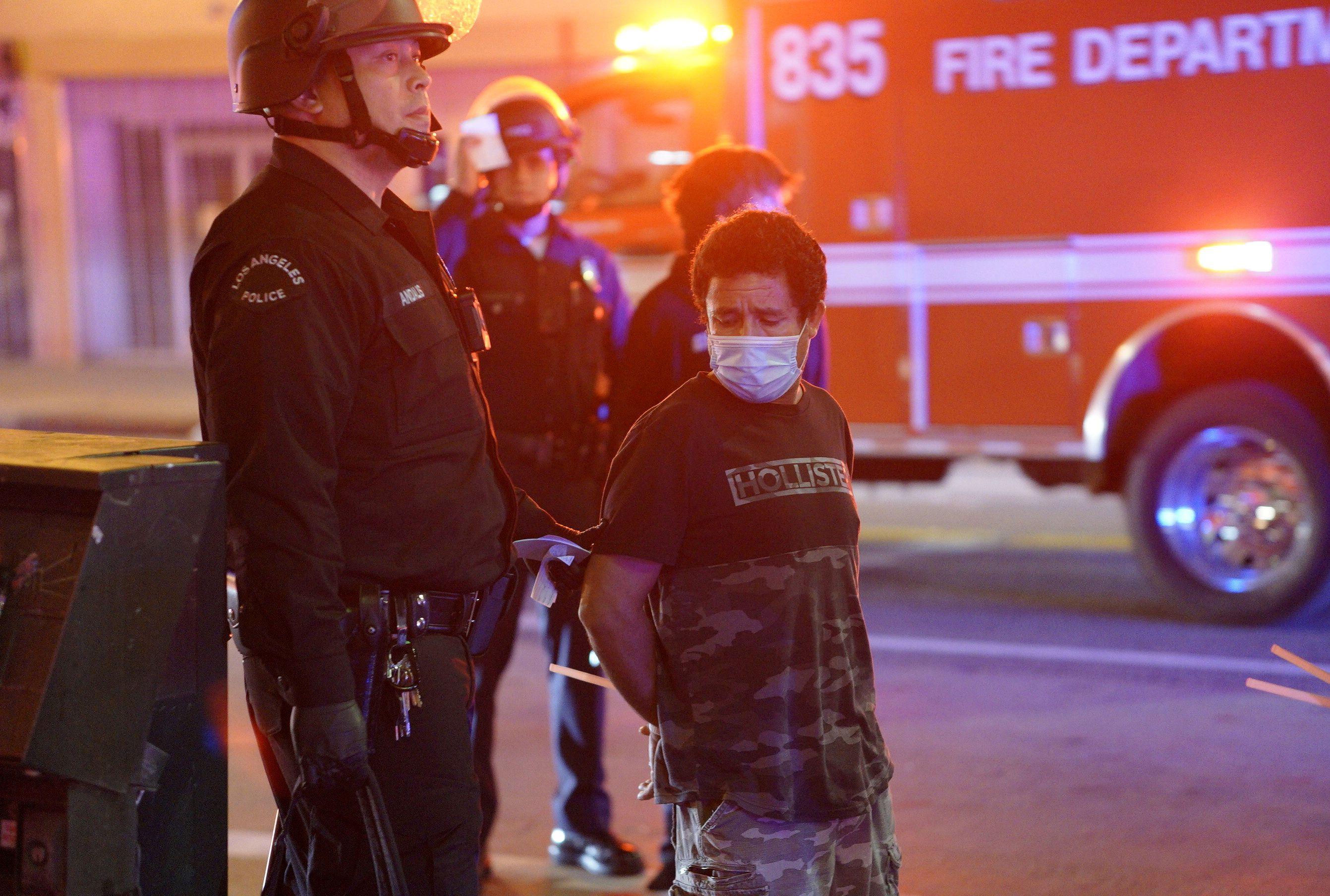 Un es detenido por oficiales durante las protestas