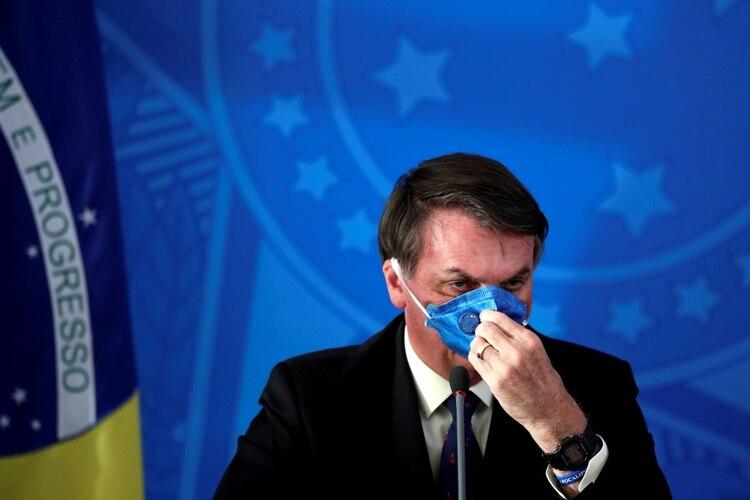 El presidente de Brasil, Jair Bolsonaro, ajusta su mascarilla protectora durante una conferencia de prensa sobre el brote de coronavirus, en Brasilia, Brasil. 20 de marzo de 2020. REUTERS/Ueslei Marcelino.