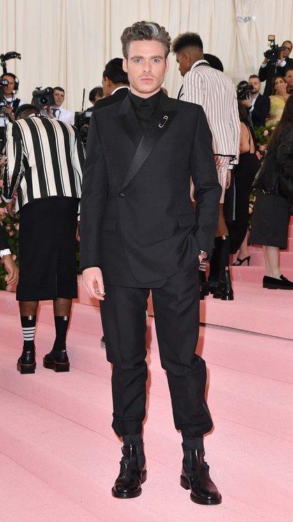 El actor escocésRichard Madden lució un elegante esmoquin negro, botas, camisa y broche de Dior Men