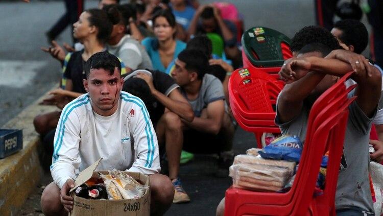 Los detenidos esperan a ser registrados por la policía, todavía con los productos que saquearon de un comercio cerrado (REUTERS/Ivan Alvarado)