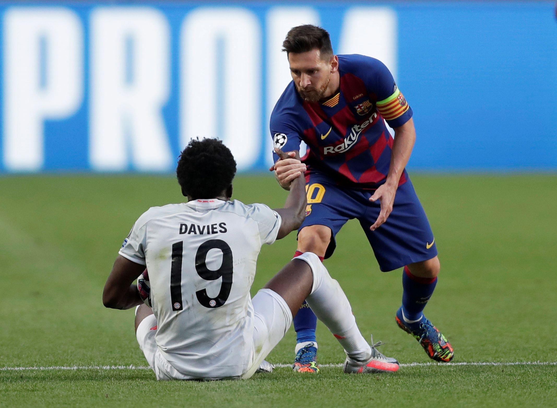 Lionel Messi ayuda a Alphonso Davies a recuperarse, durante el encuentro que disputaron Barcelona y Bayern Múnich por los cuartos de final de la Champions League y que terminó con un histórico triunfo alemán por 8-2 (Manu Fernandez / Pool vía REUTERS)