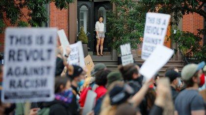 Una joven observa desde la puerta de su casa cómo se moviliza la multitud en rechazo al racismo, en Boston (REUTERS/Brian Snyder)