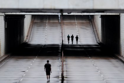 People run by an empty avenue during during a lockdown decreed by Brasilia's Governor Ibaneis Rocha to slow the rate of the coronavirus disease (COVID-19) contagion in Brasilia, Brazil, February 28, 2021. REUTERS/Ueslei Marcelino