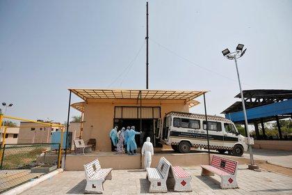 Trabajadores municipales con equipo de protección se paran como una ambulancia que lleva el cuerpo de una mujer que murió debido a la enfermedad coronavirus (COVID-19) a un crematorio en Ahmedabad, India, el 17 de abril de 2020. REUTERS/Amito Dave/Archivo Foto