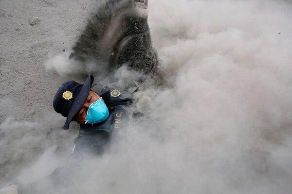 Un policía tropieza cuando corría para alejarse del flujo piroclástico, una combinación de gases volcánicos a altas temperaturas (Reuters)