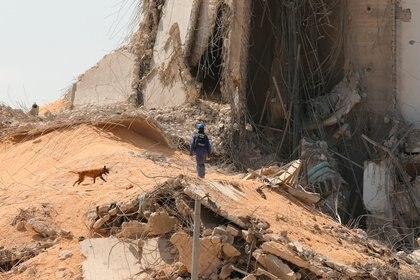 Un miembro del equipo de búsqueda y rescate busca sobrevivientes en el lugar de la explosión (REUTERS/Mohamed Azakir)