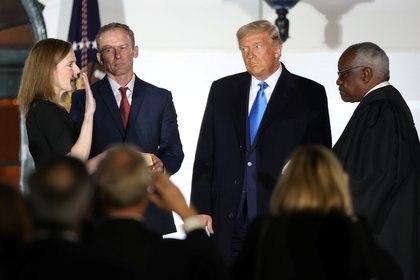La jueza Amy Coney Barrett es juramentada como juez de la Corte Suprema de los Estados Unidos por el juez de la Corte Suprema Clarence Thomas mientras su esposo Jesse Barrett y el presidente Donald Trump miran (Reuters/ Jonathan Ernst)