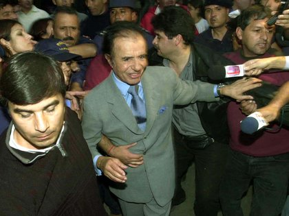 El ex candidato a presidente Carlos Menem saluda a sus simpatizantes en la residencia del gobernador Ángel Maza luego de manifestar su renuncia al ballotage en 2003