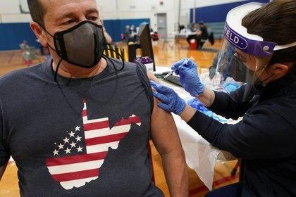 Tony Heaton, de Falling Waters, con una camiseta de Virginia Occidental con estrellas y rayas, recibe una vacuna contra la enfermedad del coronavirus (COVID-19) durante un evento de vacunación comunitaria en Martinsburg, Virginia Occidental (Reuters)