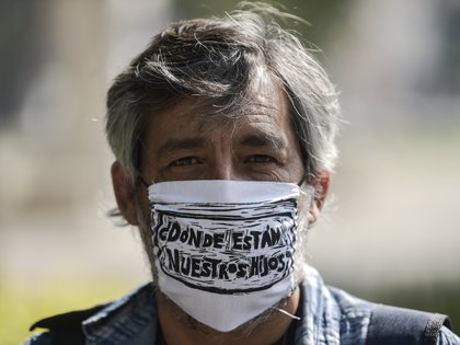 """A man with a face mask reading """"Where are our sons?"""" takes part in a march of activists and relatives of missing people to demand the Mexican government answers on the whereabouts of their loved one, as part of the commemoration of Mothers' Day in Mexico City on May 10, 2020, amid the Covid-19 coronavirus outbreak. (Photo by PEDRO PARDO / AFP)"""