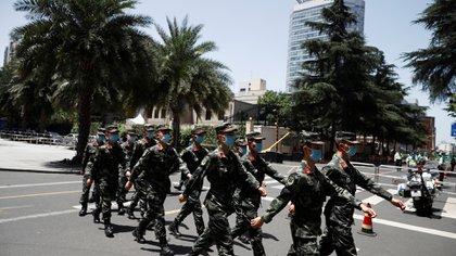 Soldados del ejército chino marchando con tapabocas (Reuters)