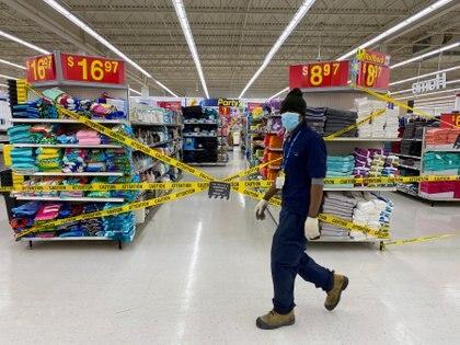 """Un empleado de Walmart camino junto a los productos marcados como """"no esenciales"""" en medio de la cuarentena (REUTERS/Carlos Osorio)"""